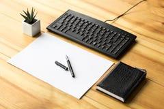 Materiale dell'ufficio con un taccuino, un foglio di carta, penna, tastiera su una tavola di legno immagini stock