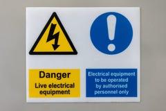 Materiale elettrico in tensione del pericolo doppio e materiale elettrico da essere segno isolato fotografia stock libera da diritti