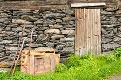Materiales de madera que se inclinan en una pared de piedra con una puerta de madera Imagen de archivo libre de regalías