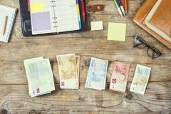 Materiales de oficina, artilugios y dinero en la tabla de madera Foto de archivo