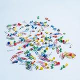 Materiales de oficina bajo la forma de botones y clips de papel coloreados Imágenes de archivo libres de regalías