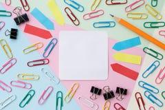 Materiales de oficina coloridos nota pegajosa, cojín de nota, clips de papel, clips de la carpeta y lápiz en fondo del color en c Fotos de archivo libres de regalías