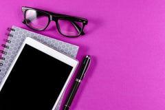 Materiales de oficina en fondo púrpura Foto de archivo