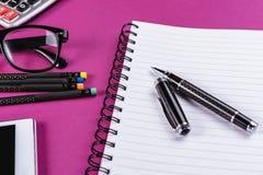 Materiales de oficina en fondo púrpura Imagen de archivo libre de regalías