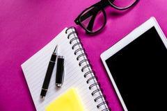 Materiales de oficina en fondo púrpura Imagenes de archivo