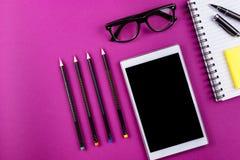 Materiales de oficina en fondo púrpura Fotografía de archivo libre de regalías
