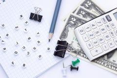 Materiales de oficina, libreta y dinero en un fondo blanco foto de archivo libre de regalías