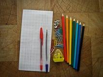 Materiales de oficina multicolores en una tabla de madera fotos de archivo