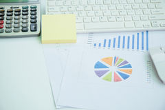 Materiales de oficina, ordenador portátil y documento en una tabla de funcionamiento blanca Foto de archivo