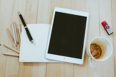 Materiales de oficina, taza de café vacía, y tableta Fotos de archivo