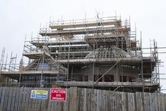 Materialet till byggnadsställning runt om nybyggnadplats och trästaketvarningsingången undertecknar royaltyfria foton