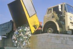 Materiali riciclabili che cadono da un camion di riciclaggio in un recipiente ad un centro di riciclaggio Fotografia Stock