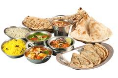 Materiel av olik indisk mat i metallbunkar och på metallplattor på vit bakgrund Royaltyfri Bild