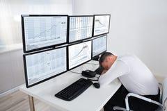 Materielaffärsman Sleeping At Multiple Computer& x27; s-skrivbord arkivfoto