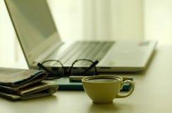 Materielfoto - kaffe, tidningar och bärbar dator i mjuk fokussettin Fotografering för Bildbyråer