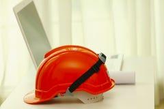 Materielfoto - orange säkerhetshjälm och norebook på den vita tabellen arkivfoton