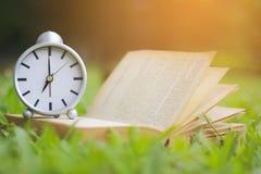 Materielfoto: Retro klocka och bok med koppen kaffe på green Royaltyfria Foton