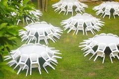 Materielfoto - vita plast- tabell och stolar utanför i en trädgård Fotografering för Bildbyråer