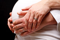 Maternal embraced hands. A loving couples embraced hans around an expectant mother stock photos