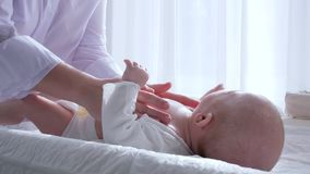 Maternal tenderness, hands of woman are doing massage to newborn in room