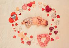 Maternal warmth. Small girl among red hearts. Love. Portrait of happy little child. Sweet little baby. New life and. Birth. Childhood happiness.Valentines day royalty free stock images