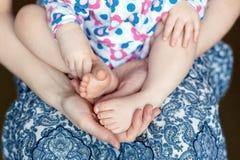 Maternidad y dulzura, piernas un pequeño bebé en la ha de su madre Fotos de archivo libres de regalías
