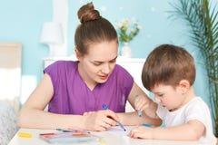 Maternidade e conceito das crianças A foto da mãe afetuosa passa o tempo com filho, estando nas licenças de parto, ensina seu m p Fotos de Stock