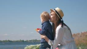Maternidade feliz, mamãe alegre de sorriso no chapéu com pouco menino da criança que aprecia fora e que olha no lago filme