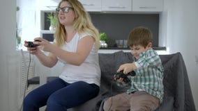 Maternidade feliz, mamãe com o filho com o controlador do jogo à disposição que joga o jogo de vídeo video estoque