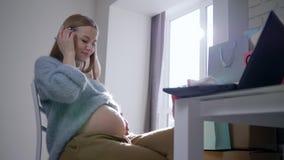 Maternidade, menina grávida bonita que afaga delicadamente sua barriga que senta-se na camiseta acolhedor em casa vídeos de arquivo