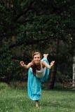 Maternità prenatale di yoga incinta che fa gli esercizi differenti nel parco sull'erba, respirare, allungante, statica Fotografia Stock