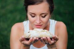 Maternité prénatale de yoga enceinte avec du pain fait maison fraîchement cuit au four dans des mains en parc sur l'herbe Images libres de droits