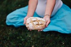Maternité prénatale de yoga enceinte avec du pain fait maison fraîchement cuit au four dans des mains en parc sur l'herbe Photo libre de droits