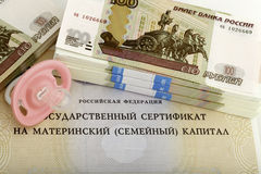 Maternity capital and baby's dummy with rolls of money. Pacifier against money and the maternal certificate stock photography