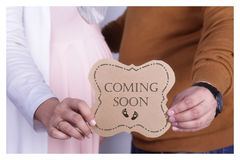 Maternity coming soon. Maternity photo shoot focus on hand of wife and husband with `coming soon` letter royalty free stock image