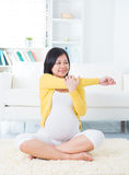 Pregnant woman yoga at home. Royalty Free Stock Photography