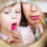 Maternity. Mother and daughter putting makeup on at home. Motherhood. Little girl imitating her mother who is applying lipstick in front of small makeup mirror royalty free stock image