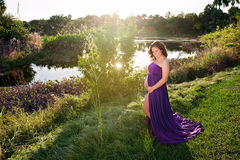 Maternity Portrait of a Woman Near a Lake's Edge. A beautiful back lit maternity portrait taken on the bank of a tropical, south Florida lake, with sun flare Stock Photo