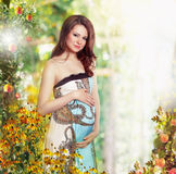 Maternity. Pregnant Smiling Woman in Nature Expecting Baby Royalty Free Stock Photography