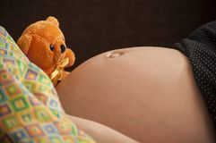 Maternity, pregnant woman with cute orange teddy bear. Maternity is love, close up shot of pregnant belly with cute orange teddy bear royalty free stock photography