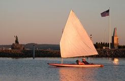 Mates. Man and a dog in a sailboat at dusk Royalty Free Stock Image