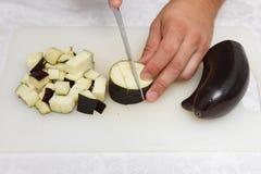 Matförberedelse - klippa aubergineet med kniven på viten Arkivbild
