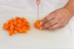 Matförberedelse - klippa carrotten med kniven på viten b Arkivbilder
