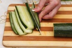 Matförberedelse - klippa gurkan Fotografering för Bildbyråer