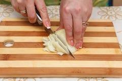 Matförberedelse - klippa lökar med kniven Arkivfoton