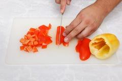 Matförberedelse - klippa spanska pepparen med kniven Arkivbilder