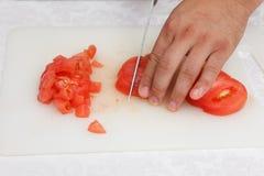 Matförberedelse - klippa tomaten med kniven Arkivbild
