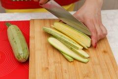 Matförberedelse - klippa zucchinin Arkivbilder