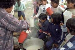 Matfördelning på indiska barn i Anderna Arkivfoto