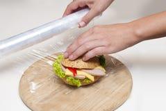 Matfilmen packar cheeseburgeren in Arkivbilder